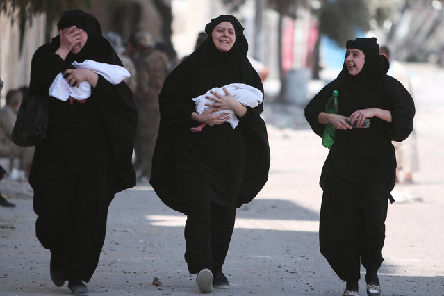 Women carry newborn babies while reacting after they were evacuated by the Syria Democratic Forces (SDF) fighters from an Islamic State-controlled neighbourhood of Manbij, in Aleppo Governorate, Syria, August 12, 2016. The SDF has said Islamic State was using civilians as human shields. (Photo by Rodi Said/Reuters)