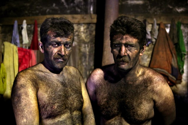 In this Wednesday, May 7, 2014 photo, Iranian coal miners pose for a photograph before taking a shower after a long day of work at a mine on a mountain in Mazandaran province, near the city of Zirab 212 kilometers (132 miles) northeast of the capital Tehran  Iran. (Photo by Ebrahim Noroozi/AP Photo)