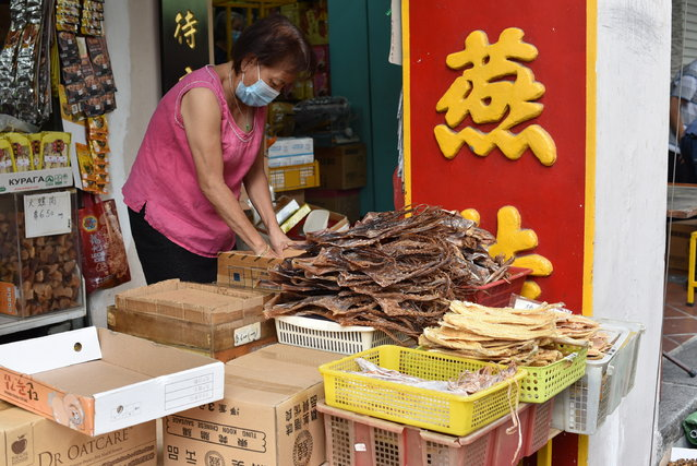 A vendor wearing a face mask prepares to display traditional Chinese medicinal products outside a Chinese medical hall in Singapore's Chinatown district on Tuesday, May 12, 2020. Singapore has allowed selected businesses such as traditional Chinese medicine medical halls, home-based establishments, food manufacturing, selected food retail outlets, laundry services, traditional barbers and pet supplies to reopen May 12 in a cautious rollback of a two-month partial lockdown to curb the spread of COVID-19 infections in the city-state. (Photo by Y.K. Chan/AP Photo)