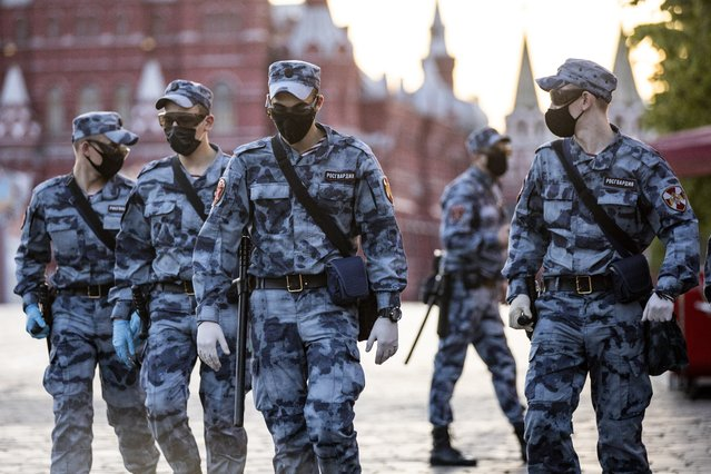 Russian Rosguardia (National Guard) soldiers wearing face masks and gloves to protect against coronavirus, guard an area on Red Square before a rehearsal of the military parade near Red Square in Moscow, Russia, Sunday, June 14, 2020. Last month, Putin ordered an end to the nationwide economic shutdown and set dates for the two main events on his agenda that were postponed due to the coronavirus. (Photo by Alexander Zemlianichenko/AP Photo)