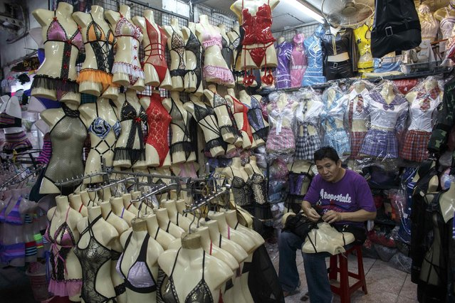 A shopkeeper puts up lingerie on a mannequin at his shop in a shopping mall in Bangkok October 7, 2014. Picture taken October 7, 2014. (Photo by Athit Perawongmetha/Reuters)
