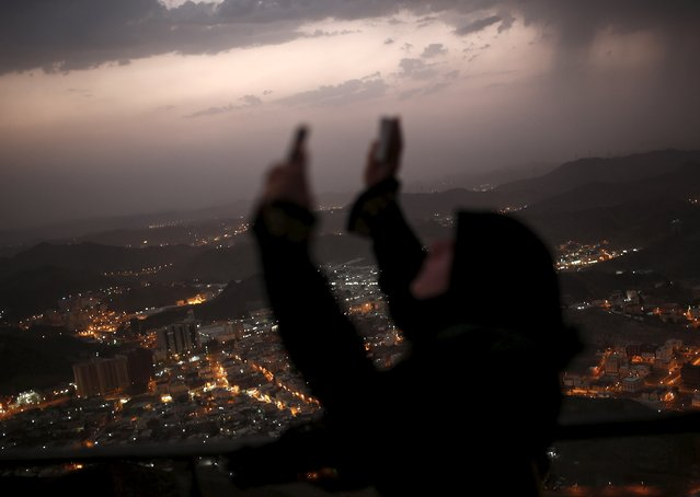 A Muslim pilgrim raises her hands to pray after visiting Hera cave, where Muslims believe Prophet Mohammad received the first words of the Koran through Gabriel, at the top of Mount Al-Noor during the annual haj pilgrimage in the holy city of Mecca, September 21, 2015. (Photo by Ahmad Masood/Reuters)