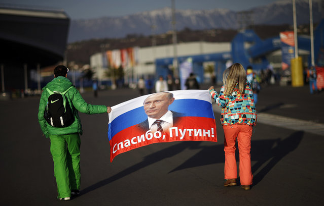 """In this February 23, 2014 file photo Veleriya Obarevich, right, and Yan Shamilov carry a Russian flag with the message """"Thank you, Putin!"""" written across it in Russian through Olympic Park ahead of the 2014 Winter Olympics closing ceremony  in Sochi, Russia. Russia could be banned from competing at the Pyeongchang Olympics. The decision will come on Tuesday, December 5, 2017 when the International Olympic Committee executive board meets in Lausanne, less than nine weeks before the games open on Feb. 9 in South Korea. (Photo by David Goldman/AP Photo)"""
