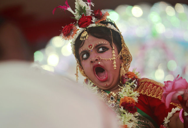 Satarupa Chakraborty, 5, dressed as a Kumari, yawns while she is worshipped by a Hindu priest during the religious festival of Durga Puja in Agartala October 2, 2014. (Photo by Jayanta Dey/Reuters)