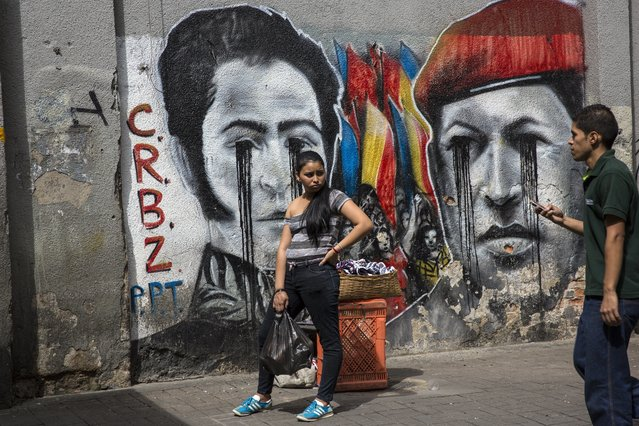 A woman stands in front of graffiti depicting Venezuela's late former President Hugo Chavez, right, and revolutionary hero Simon Bolivar, in downtown Caracas, Venezuela, Wednesday, October 25, 2017. (Photo by Rodrigo Abd/AP Photo)