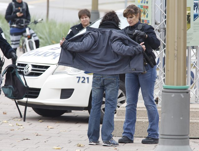 Police search cars and pedestrians as they leave the Alexandra Bridge and enter Gatineau, Quebec near the Parliament Buildings in Ottawa on Wednesday, October 22, 2014. (Photo by Patrick Doyle/AP Photo/The Canadian Press)