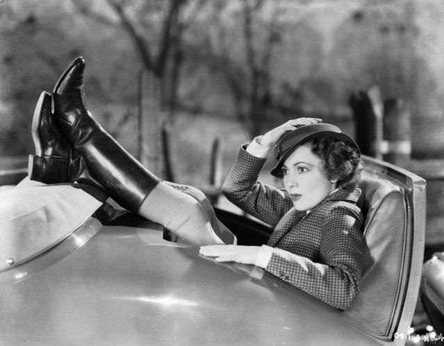 British-born actress Olivia de Havilland squeezes into the back seat of a convertible, circa 1936. (Photo via John Kobal Foundation/Getty Images)