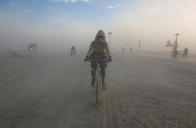 Participants travel through the dust as approximately 70,000 people from all over the world gathered for the 30th annual Burning Man arts and music festival in the Black Rock Desert of Nevada, U.S. September 4, 2016. (Photo by Jim Urquhart/Reuters)