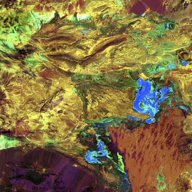 """Dasht-e Kavir, Iran. Like poster paints run wild, this image reveals an eclectic montage of landscapes in Iran's largest desert, the Dasht-e Kavir, or Great Salt Desert. The word """"kavir"""" is Persian for """"salt marsh"""". The almost uninhabited region covers an area of more than 77,000 square kilometres and is a mix of dry streambeds, desert plateaus, mudflats, and salt marshes. Extreme heat, dramatic daily temperature swings, and violent storms are the norm in this inhospitable place. Image taken February 10, 2003, by Landsat 7. (Photo by NASA/GSFC/USGS EROS Data Center)"""