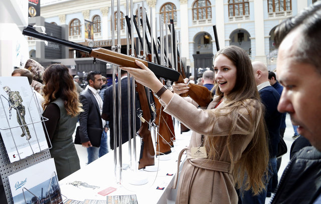A visitor aims with a rifle on display at the Kalashnikov Group pavilion during the ARMS & Hunting 2015 International Exhibition at the Gostinniy Dvor exhibition centre in Moscow, Russia, October 2, 2015. (Photo by Maxim Shipenkov/EPA)