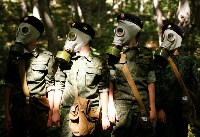 Fifth-grade students of the General Yermolov Cadet School wear gas masks during their first military tactical exercise on the ground, which includes radiation resistance classes, forest survival studies and other activities, in Stavropol, Russia, September 10, 2016. Picture taken September 10, 2016. (Photo by Eduard Korniyenko/Reuters)