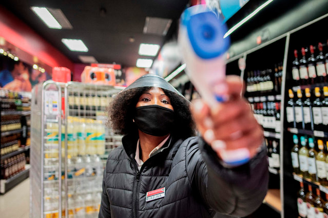 A liquor store worker measures temperatures of customers at the entrance of a shop in Melville, Johannesburg, on August 18, 2020. South Africa moved into level two of a five-tier lockdown on August 18, 2020, to continue efforts to curb the spread of the COVID-19 coronavirus. Under level two liquor and tobacco sales will resume. (Photo by Luca Sola/AFP Photo)