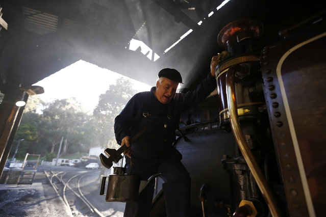 Puffing Billy steam engine driver Steve Holmes, 61, climbs down from his locomotive in the morning light during an inspection before running a train from Belgrave near Melbourne, October 20, 2014. But in one small corner of rural Australia, the sights, sounds and smells of the Industrial Revolution remain very much alive. (Photo by Jason Reed/Reuters)