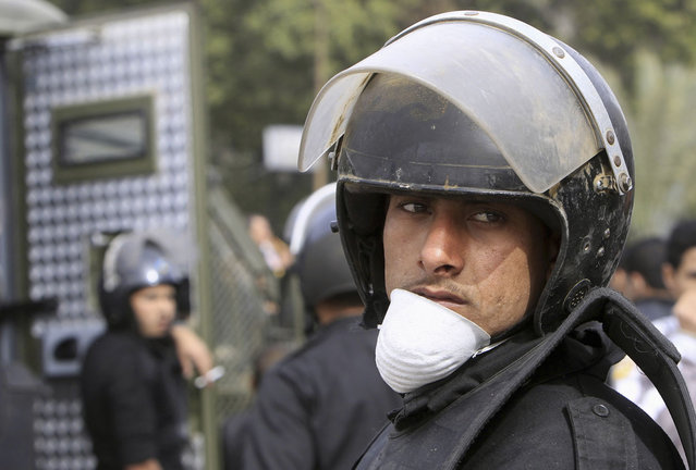 A riot police officer looks on during clashes between protesters opposing Egyptian President Mohamed Morsi, and riot police with other Egyptians fighting alongside them, along Qasr Al Nil bridge, in Cairo, on January 27, 2013. (Photo by Mohamed Abd El Ghany/Reuters/The Atlantic)