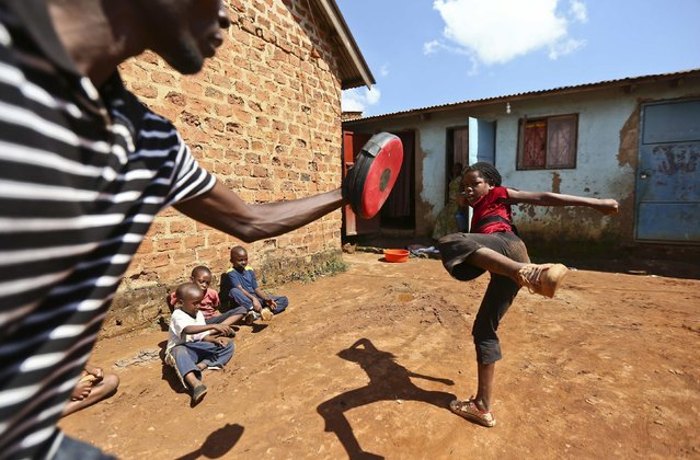A trainer helps Kirabo Beatrice as she rehearses her acting moves during a martial arts class organised by local non-governmental organisations (NGOs) and residents, in the Wakaliga slums of Uganda's capital Kampala, November 1, 2014. The slum-based children are trained to take up acting roles in movies which cover issues affecting their communities like child sacrifice, poverty, and theft among others. (Photo by Edward Echwalu/Reuters)