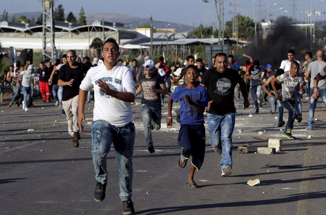 Palestinian protesters run for cover during clashes with Israeli troops in the West Bank city of Jenin October 9, 2015. (Photo by Mohammed Ballas/Reuters)