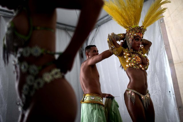 """Prado gets into her costume as she prepares for the parade. Though samba dancers, or """"passistas"""", as they're known in Portuguese, are unquestionably the star attractions of the world's most iconic Carnival celebrations, they're not on the payroll of the samba school they represent. (Photo by Felipe Dana/Associated Press)"""