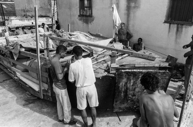 Rolando Pujol Rodriguez photographed the Cuban raft exodus in 1994, and twenty years later Enrique de la Osa took portraits of some of the people who made it to the United States, in this story which combines archive and present day images. Here: People put the finishing touches to a makeshift boat on a rooftop before lowering it onto a truck and launching it into the Straits of Florida towards the U.S., on the last day of the 1994 Cuban raft exodus in Havana, in this September 13, 1994 file photo. (Photo by Rolando Pujol Rodriguez/Reuters)