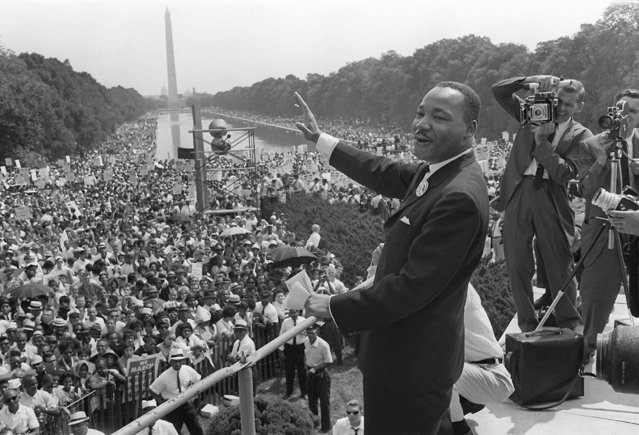 "The civil rights leader Martin Luther KIng (C) waves to supporters 28 August 1963 on the Mall in Washington DC (Washington Monument in background) during the ""March on Washington"". King said the march was ""the greatest demonstration of freedom in the history of the United States"". (Photo by  AFP Photo)"