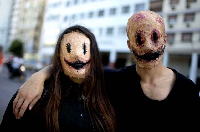 """A couple wearing masks pose for a portrait as they participate in the Argentina Zombie Walk in Buenos Aires, Argentina, Sunday, November 16, 2014. The procession of the """"living dead"""" is an annual solidarity event in which every participant is asked to bring food that will be donated to a common dinning room from a Buenos Aires shantytown. (Photo by Natacha Pisarenko/AP Photo)"""