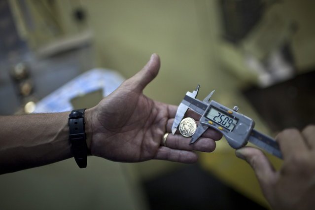 A worker checks the diameter of a R$ 0.25 coin, or 25 centavo, at the Casa da Moeda, the national mint, in the Santa Cruz suburb of Rio de Janeiro, Brazil, on Tuesday, March 5, 2013. Brazil is likely to keep its key interest rate at a record low for the third straight meeting, as policy makers are caught between a fragile economic recovery and faster-than-expected inflation. (Photo by Dado Galdieri/Bloomberg)