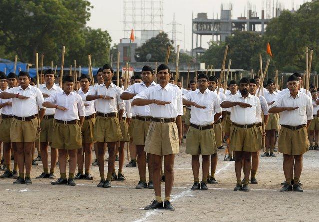 "Volunteers of the Hindu nationalist organisation Rashtriya Swayamsevak Sangh (RSS) salute as they take part in the ""Path-Sanchalan"", or Volunteer March during celebrations to mark the Vijaya Dashmi or Dussehra in Ahmedabad, India, October 18, 2015. (Photo by Amit Dave/Reuters)"