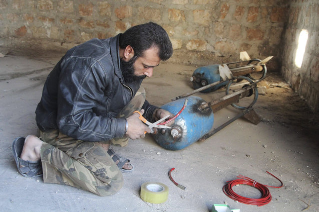A Free Syrian Army fighter prepares a locally made shell before firing it towards forces loyal to Syria's President Bashar al-Assad in Bani Zeid neighborhood, Aleppo November 10, 2014. (Photo by Abdalrhman Ismail/Reuters)