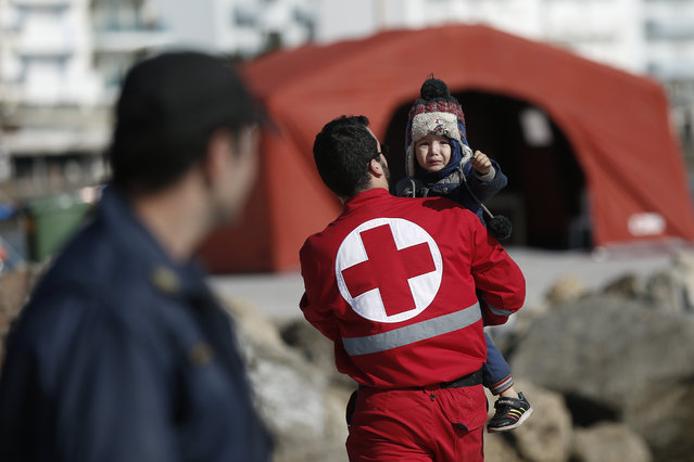 A Red Cross volunteer carries a child just disembarked from a crippled freighter carrying hundreds of refugees trying to migrate to Europe, at the coastal Cretan port of Ierapetra, Greece, on Thursday, November 27, 2014. The ship, whose 750 passengers are mostly Syrians,  including children, women and elderly men, suffered engine failure 70 nautical miles off Ierapetra on Tuesday. The migrants will be given temporary shelter at an Ierapetra indoor basketball stadium. (Photo by Petros Giannakouris/AP Photo)
