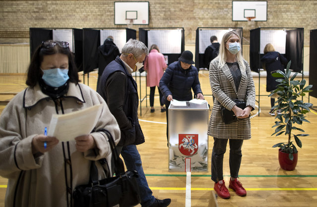 People wear face masks to protect against coronavirus as they cast their ballots during the parliamentary elections in Vilnius, Lithuania, Sunday, October 11, 2020. Polls opened Sunday for the first round of national election in Lithuania, where voters will renew the 141-seat parliament and the ruling four-party coalition is widely expected to face a stiff challenge from the opposition to remain in office. (Photo by Mindaugas Kulbis/AP Photo)
