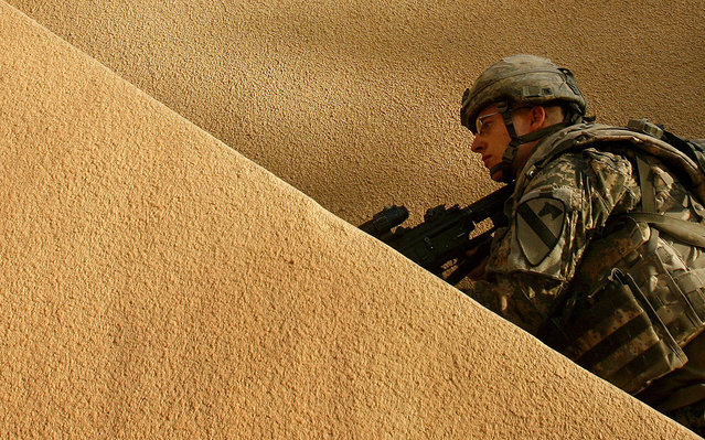 U.S. Army Pvt. Joe Armstrong of Alpha Company, 1st Battalion, 5th Cavalry Regiment, 2nd Brigade, 1st Cavalry Division searches the rooftop of a house during an operation in the Amariyah neighborhood of west Baghdad, Iraq, on Monday, August 13, 2007. (Photo by Petr David Josek/AP Photo/The Atlantic)