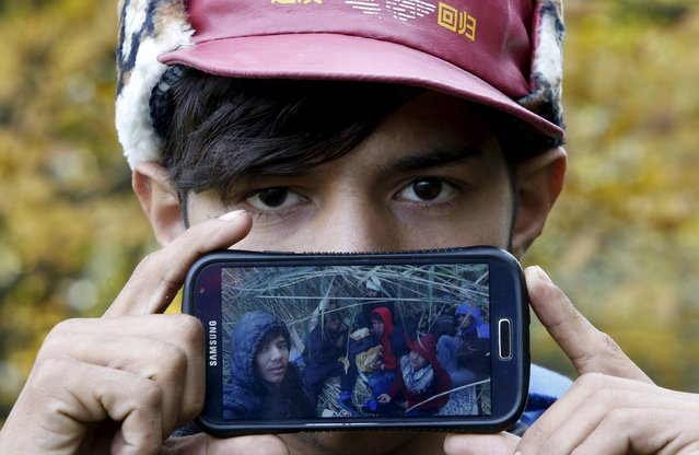 Migrant Akram from Herat, Afghanistan, shows a picture of his frinds on their journey to Europe as he waits to cross the Slovenia-Austria border in Sentilj, Slovenia October 25, 2015. (Photo by Srdjan Zivulovic/Reuters)