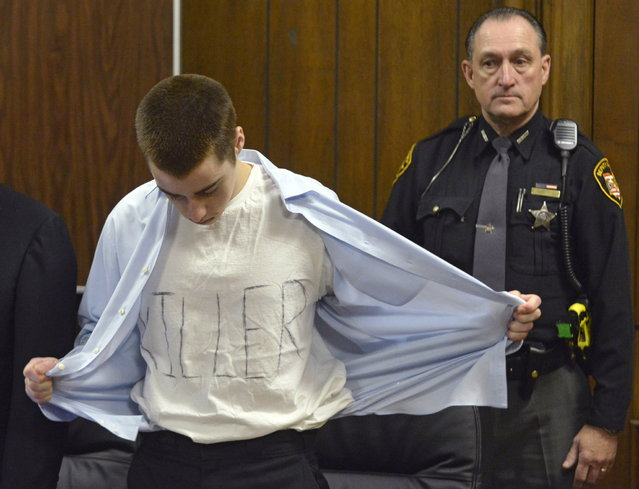 T.J. Lane unbuttons his shirt during sentencing Tuesday, March 19, 2013, in Chardon, Ohio.  Lane, was given three lifetime prison sentences without the possibility of parole Tuesday for opening fire last year in a high school cafeteria in a rampage that left three students dead and three others wounded. Lane, 18, had pleaded guilty last month to shooting at students in February 2012 at Chardon High School, east of Cleveland. Investigators have said he admitted to the shooting but said he didn't know why he did it. Before the case went to adult court last year, a juvenile court judge ruled that Lane was mentally competent to stand trial despite evidence he suffers from hallucinations, psychosis and fantasies. (Photo by Duncan Scott/AP Photo/The News-Herald/Pool)