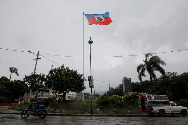 A motorcyclist drives next to a flag of Haiti while Hurricane Matthew approaches in Port-au-Prince, Haiti, October 3, 2016. (Photo by Carlos Garcia Rawlins/Reuters)