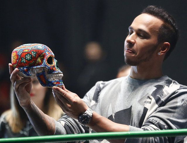 Mercedes Formula One driver Lewis Hamilton of Britain looks at a traditional Day of the Dead Mexican skull adorned with Mexican crafts at the Coliseo Arena during a promotional event in Mexico City, October 28, 2015. Formula One racing will return to Mexico on November 1, 2015 at the Hermanos Rodriguez circuit in Mexico City, according to local media. (Photo by Henry Romero/Reuters)