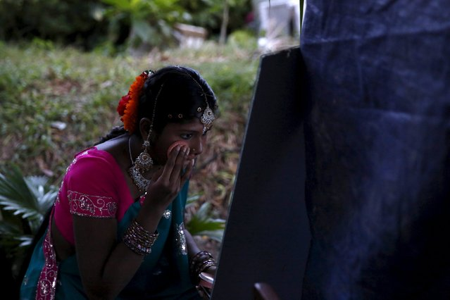 A dancer puts on make up before going on stage for a Diwali performance in Kuala Lumpur, Malaysia, October 28, 2015. (Photo by Olivia Harris/Reuters)