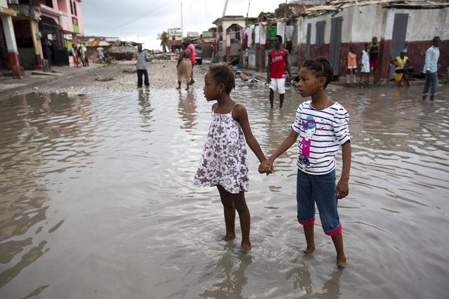 Girls hold hands as they help each other wade through a flooded street after the passing of Hurricane Matthew in Les Cayes, Haiti, Thursday, October 6, 2016. Two days after the storm rampaged across the country's remote southwestern peninsula, authorities and aid workers still lack a clear picture of what they fear is the country's biggest disaster in years. (Photo by Dieu Nalio Chery/AP Photo)