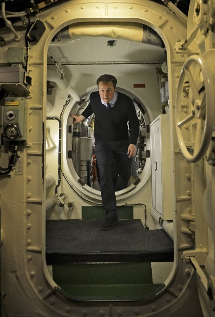 Britain's Prime Minister David Cameron walks through compartments on board the nuclear submarine HMS Victorious off the west coast of Scotland April 4, 2013. Cameron reopened a rift in his coalition government over the future of Britain's nuclear deterrent on Thursday, saying potential threats from countries such as Iran and North Korea meant it could not be scaled back. (Photo by Tom Robinson/Reuters/Crown Copyright)