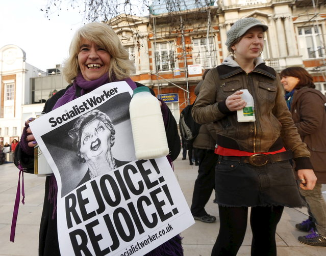 "Revellers hold up posters and cartons of milk to celebrate the death of Britain's former prime minister Margaret Thatcher in Brixton, south London April 8, 2013. Margaret Thatcher, the ""Iron Lady"" who transformed Britain and inspired conservatives around the world by radically rolling back the state during her 11 years in power, died on Monday following a stroke. She was 87. (Photo by Olivia Harris/Reuters)"