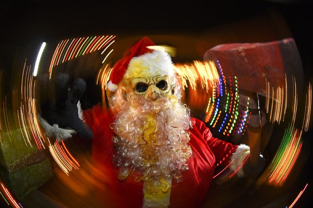 A Zombie Santa is pictured Death Yard Haunted Attraction in Hendersonville, Tennessee December 10, 2014. The Nashville-area haunted house is getting into the Christmas spirit this weekend, with Zombie Santa, his undead elves and a demonic reindeer going on the attack for fun and charity. Picture taken with slow shutter speed and panning motion. (Photo by Harrison McClary/Reuters)
