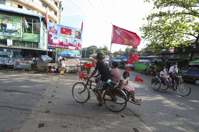 A trishaw with passengers onboard pass in front of a campaign billboard for candidates of the National League for Democracy party in Yangon, Myanmar, on Thursday, November 5, 2020. (Photo by Thein Zaw/AP Photo)