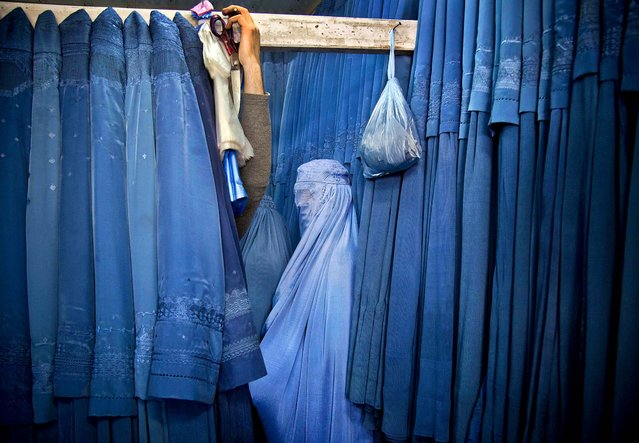 A woman waits in a changing room to try out a new Burqa, in a shop at in the old city of Kabul, Afghanistan, on April 11, 2013. (Photo by Anja Niedringhaus/Associated Press)