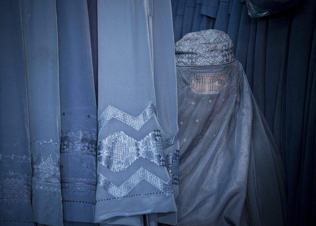 In this Thursday, April 11, 2013 photo, an Afghan woman peers through the  the eye slit of her burqa as she waits to try on a new burqa in shop in the old town of Kabul, Afghanistan. (Photo by Anja Niedringhaus/AP Photo)