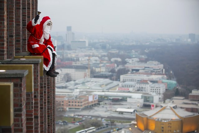 A man dressed as a Santa Claus poses at the front of the Kollhoff Tower at Potsdamer Platz square in Berlin December 14, 2014. (Photo by Hannibal Hanschke/Reuters)