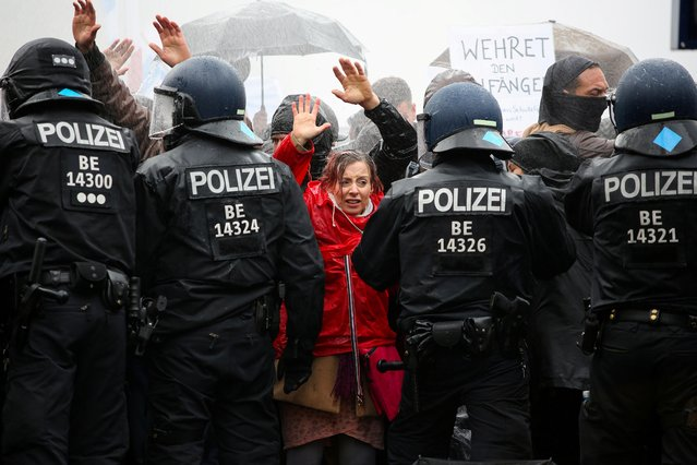Demonstrators put up their hands in front of police officers during a protest against the government's coronavirus disease (COVID-19) restrictions, near the Brandenburger Gate in Berlin, November, 18, 2020. (Photo by Christian Mang/Reuters)