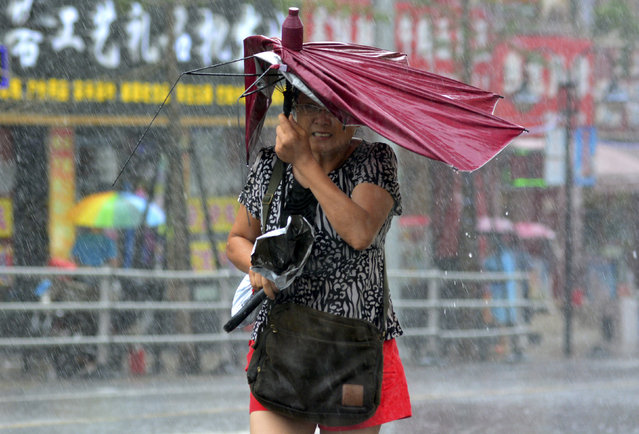 A woman holds her broken umbrella as she walks against strong wind and heavy rainfall as Typhoon Matmo hit Qingdao, Shandong province, China, July 25, 2014. (Photo by Reuters/Stringer)