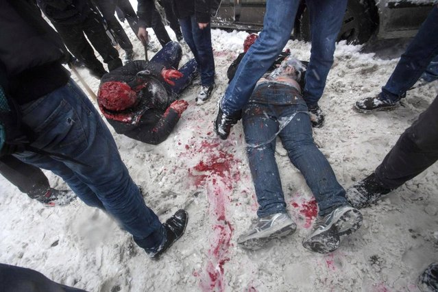 In this photo taken on Friday, March 15, 2013, members of a pro-Kremlin youth group douse with red paint two tied-up pushers of spice, a synthetic drug, in Moscow, Russia. Russian officials and anti-drugs campaigners say that spice has become one of the most dangerous drugs widely available to youngsters and almost impossible to ban because of the constantly changing chemical ingredients. (Photo by Alexander Zemlianichenko Jr/AP Photo)