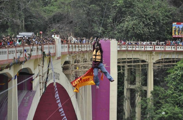 In this Sunday, April 28, 2013 photograph, people watch as Indian Sailendra Nath Roy attempts to cross Teesta river suspended from a zip wire attached to his ponytail moments before his death in Siliguri, West Bengal state, India. Roy who was named a Guinness World Record holder in 2011 for travelling the farthest distance on a zip wire using hair died during the stunt Sunday when he suffered a heart attack. (Photo by AP Photo)