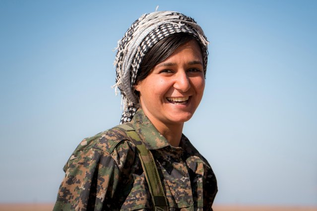 A Kurdish female fighter from the People's Protection Units (YPG) smiles as she stands near the al-Hawl area where fighting between Islamic State fighters and fighters from Democratic Forces of Syria are taking place in south-eastern city of Hasaka, Syria November 10, 2015. (Photo by Rodi Said/Reuters)