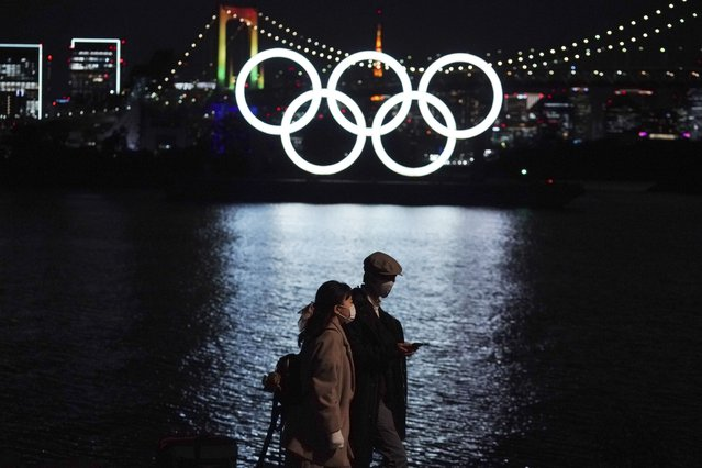 A man and a woman walk past near the Olympic rings floating in the water in the Odaiba section Tuesday, December 1, 2020, in Tokyo. The Olympic Symbol was reinstalled after it was taken down for maintenance ahead of the postponed Tokyo 2020 Olympics. (Photo by Eugene Hoshiko/AP Photo)