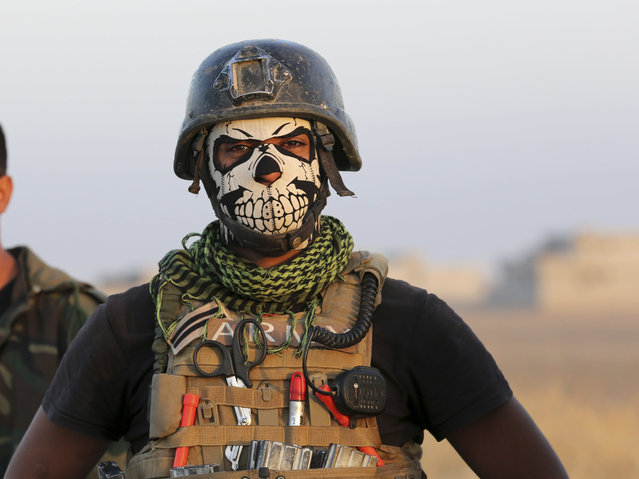 A member of Iraq's elite counterterrorism forces stands as they advance towards the city of Mosul, Iraq, Thursday, October 20, 2016. Iraqi special forces charged into the Mosul battle Thursday with a pre-dawn advance on a nearby town held by the Islamic State group, a key part of a multi-pronged assault on eastern approaches to the besieged city. (Photo by Khalid Mohammed/AP Photo)